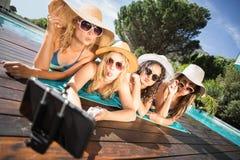 Amigos felices que gozan en la piscina Fotos de archivo libres de regalías