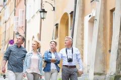 Amigos felices que hablan mientras que camina en ciudad Fotografía de archivo libre de regalías