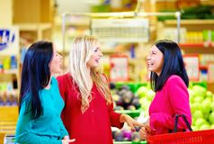 Amigos felices que hacen compras junto en supermercado del ultramarinos fotografía de archivo