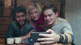 Amigos felices que hacen la llamada video con el teléfono móvil en café almacen de video