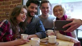 Amigos felices que hacen la llamada video con el teléfono móvil en café metrajes
