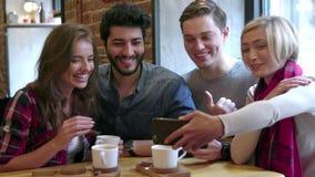 Amigos felices que hacen la llamada video con el teléfono móvil en café almacen de metraje de vídeo