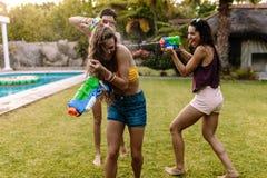 Amigos felices que hacen tiroteo del agua en el poolside foto de archivo libre de regalías