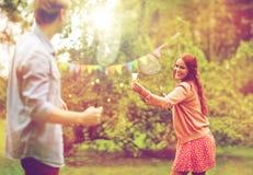 Amigos felices que juegan a bádminton en el jardín del verano Foto de archivo libre de regalías