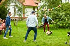 Amigos felices que juegan con el perro en el jardín del verano Imagen de archivo
