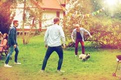 Amigos felices que juegan con el perro en el jardín del verano Foto de archivo