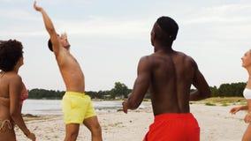 Amigos felices que juegan la bola en la playa del verano almacen de video