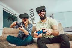 Amigos felices que juegan a los videojuegos con los vidrios de la realidad virtual imagenes de archivo