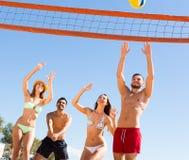 Amigos felices que juegan a voleibol en la playa Foto de archivo
