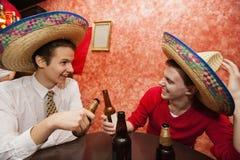 Amigos felices que llevan los sombreros mexicanos que tuestan en la tabla del restaurante Imagen de archivo