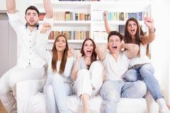 Amigos felices que miran el partido de fútbol en la TV Fotografía de archivo libre de regalías