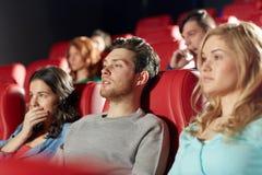 Amigos felices que miran película de terror en teatro Foto de archivo