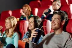 Amigos felices que miran película en teatro Foto de archivo