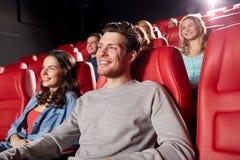 Amigos felices que miran película en teatro Fotografía de archivo