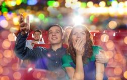 Amigos felices que miran película en teatro Imagen de archivo