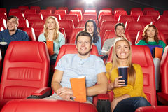 Amigos felices que miran película en teatro Imágenes de archivo libres de regalías