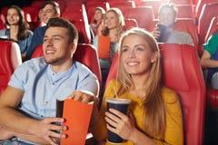 Amigos felices que miran película en teatro Fotografía de archivo libre de regalías