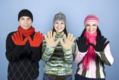 Amigos felices que muestran las palmas en guantes Foto de archivo
