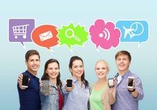 Amigos felices que muestran las pantallas en blanco de los smartphones Imágenes de archivo libres de regalías