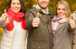 Amigos felices que muestran los pulgares para arriba en parque del otoño Fotos de archivo libres de regalías