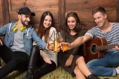 Amigos felices que pasan su tiempo con las bebidas de la guitarra y del alcohol Fotografía de archivo