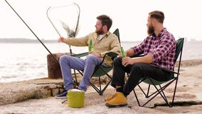 Amigos felices que pescan y que beben la cerveza en el embarcadero metrajes