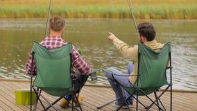 Amigos felices que pescan y que beben la cerveza en el lago almacen de video