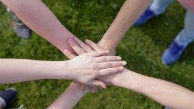 Amigos felices que ponen sus manos encima de uno a en la hierba en el fondo que simboliza la unidad y el trabajo en equipo almacen de video
