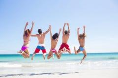 Amigos felices que saltan junto fotografía de archivo