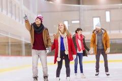Amigos felices que señalan el finger en pista de patinaje Imagen de archivo libre de regalías