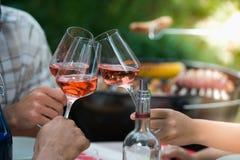 Amigos felices que se divierten al aire libre, manos que tuestan la copa de vino color de rosa Imagen de archivo libre de regalías