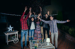 Amigos felices que se divierten entre el confeti del partido Fotografía de archivo