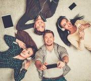 Amigos felices que se relajan con los artilugios Foto de archivo libre de regalías
