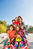 Amigos felices que se sientan con los monopatines y los cascos Fotografía de archivo libre de regalías