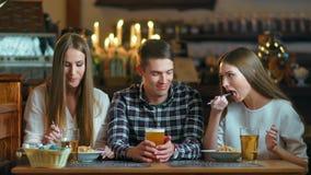 Amigos felices que se sientan en café mientras que come y bebe el alcohol almacen de video