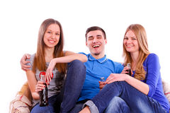 Amigos felices que se sientan en el sofá y la soda de consumición Fotos de archivo