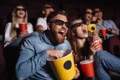 Amigos felices que se sientan en película del reloj del cine Foto de archivo
