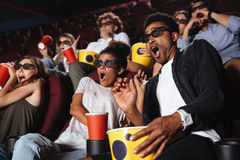 Amigos felices que se sientan en película del reloj del cine Fotos de archivo libres de regalías
