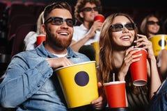 Amigos felices que se sientan en película del reloj del cine Imagen de archivo