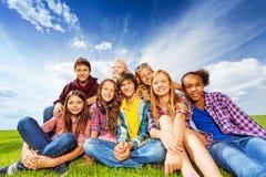 Amigos felices que se sientan en prado verde Foto de archivo libre de regalías