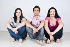 Amigos felices que se sientan en un hogar de la fila Foto de archivo libre de regalías