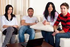 Amigos felices que sientan el sofá fotografía de archivo libre de regalías