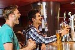 Amigos felices que sientan y que beben la cerveza Imagen de archivo libre de regalías