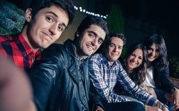 Amigos felices que sonríen y que toman el selfie en partido Imagenes de archivo