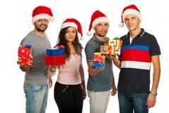 Amigos felices que sostienen los regalos de la Navidad Foto de archivo libre de regalías