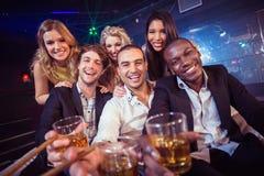 Amigos felices que sostienen un vidrio de alcohol Foto de archivo libre de regalías