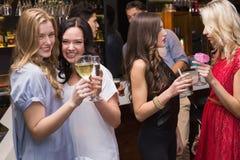 Amigos felices que tienen una bebida junto Foto de archivo libre de regalías