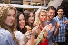 Amigos felices que tienen una bebida junto Imagen de archivo libre de regalías
