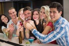 Amigos felices que tienen una bebida junto Imágenes de archivo libres de regalías