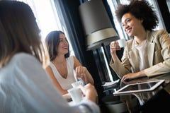 Amigos felices que tienen una buena conversación que se sienta en un restaurante fotografía de archivo